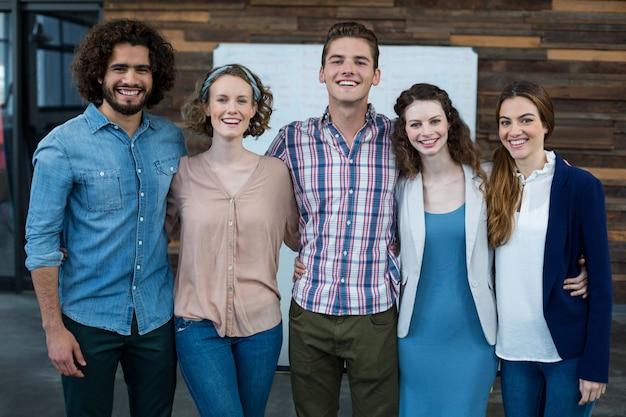 Lächelnde geschäftsleute, die zusammen mit arm im büro stehen