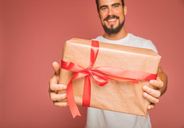 Lächelnde geschenkbox des lächelnden mannes mit rotem bandbogen gegen farbigen hintergrund