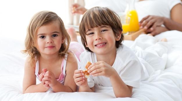 Lächelnde geschwister, die frühstücken