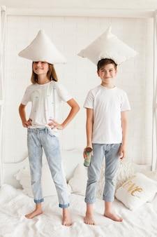Lächelnde geschwister, die mit kissen auf ihrem kopf im schlafzimmer stehen