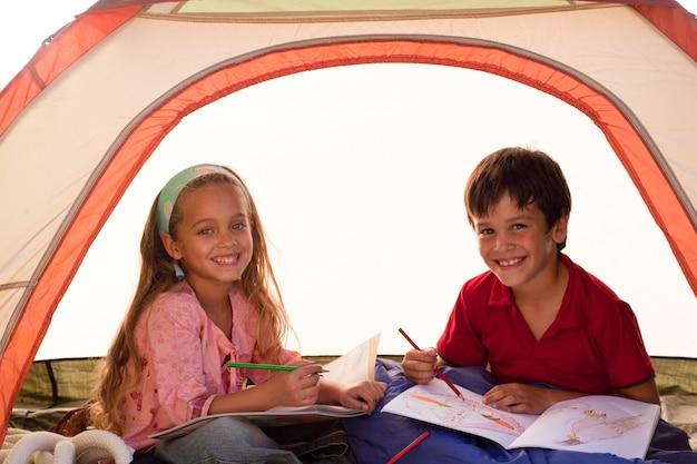 Lächelnde geschwister in einem zelt