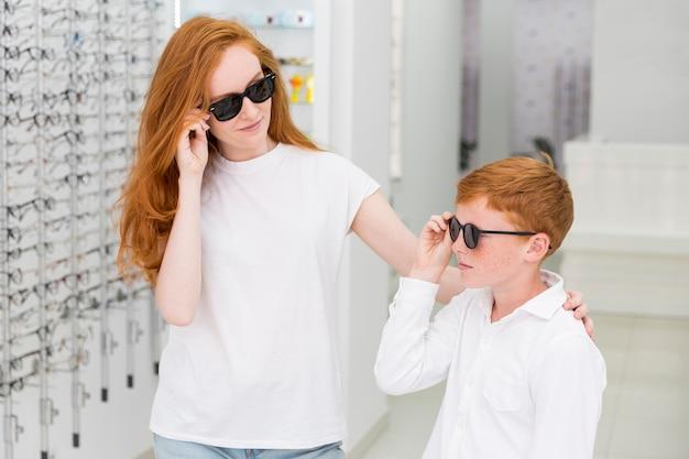 Lächelnde geschwister mit den schwarzen brillen, die im optikspeicher aufwerfen