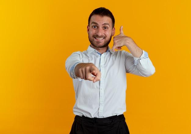 Lächelnde gesten des gutaussehenden mannes nennen mich handzeichen, das lokal auf orange wand zeigt