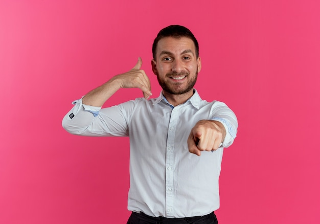 Lächelnde gesten des gutaussehenden mannes nennen mich handzeichen, das lokal auf rosa wand zeigt