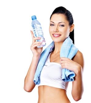 Lächelnde gesunde frau mit flasche wasser und handtuch. gesundes lebensstilkonzept.
