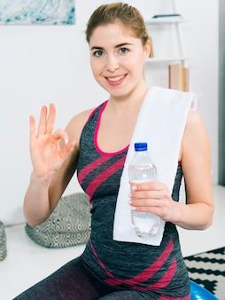 Lächelnde gesunde junge frau, die in der hand wasserflasche zeigt okayzeichen hält