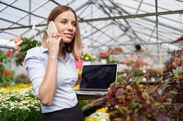 Lächelnde gewächshausbesitzerin posiert mit einem laptop in ihren händen, die am telefon mit vielen blumen und glasdach sprechen.