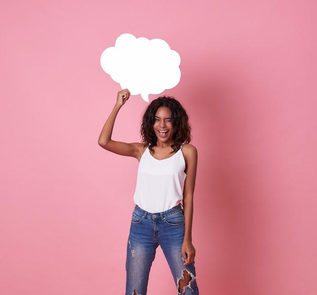 Lächelnde glückliche afrikanische frau, die leere spracheblase hält und die kamera auf rosa betrachtet.