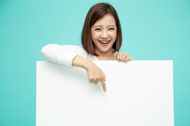 Lächelnde glückliche asiatin, die hinter großem weißem plakat steht und finger unten auf das leere copyspace lokalisiert auf hellgrünem zeigt