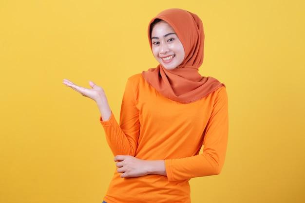 Lächelnde glückliche asiatische frau etwas in ihrer hand und präsentiert es auf hellgelbem fahnenhintergrund, der hijab trägt
