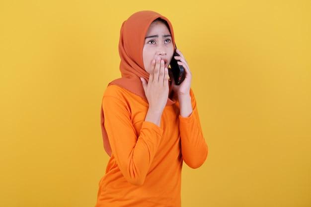 Lächelnde glückliche asiatische frau mit geflüstertem ausdruck einzeln auf hellgelbem bannerhintergrund mit hijab, mit handy sprechend