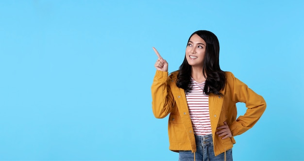 Lächelnde glückliche asiatische frau mit ihrem finger, der lokalisiert auf hellblauem fahnenhintergrund mit kopienraum zeigt.