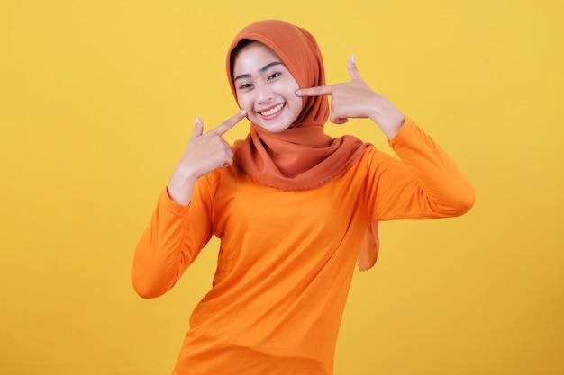 Lächelnde glückliche asiatische frau mit ihrem finger zeigt lächelnd nach oben isoliert auf hellgelbem bannerhintergrund mit hijab