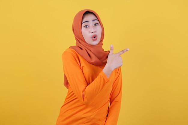 Lächelnde glückliche asiatische frau mit ihrem fingerzeig isoliert auf hellgelbem bannerhintergrund mit hijab