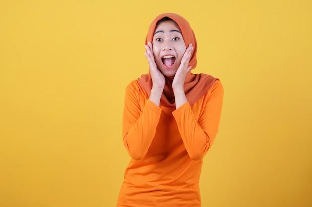 Lächelnde glückliche asiatische frau mit ihrem überraschenden ausdruck einzeln auf hellgelbem bannerhintergrund mit hijab