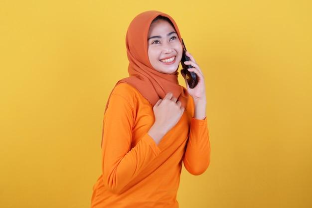 Lächelnde glückliche asiatische frau mit isoliert auf hellgelbem bannerhintergrund, die hijab trägt und mit handy spricht