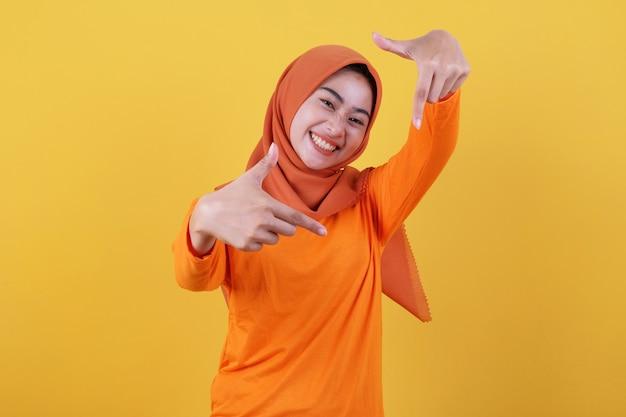 Lächelnde glückliche asiatische frau mit nahaufnahmegeste mit gelbem hintergrund