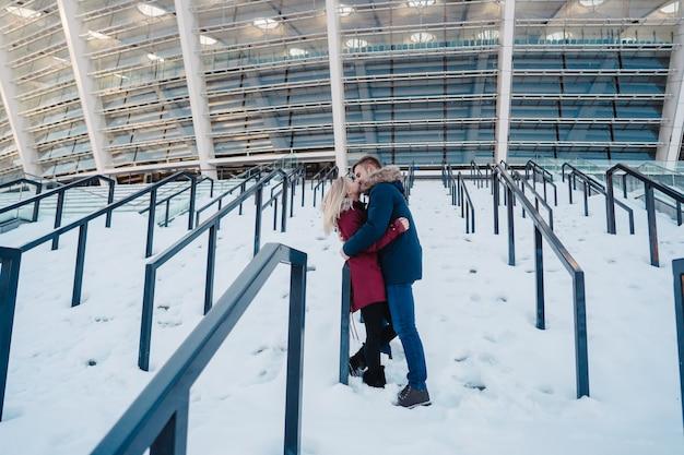 Lächelnde glückliche europäische paare der junge, die im winter umarmen