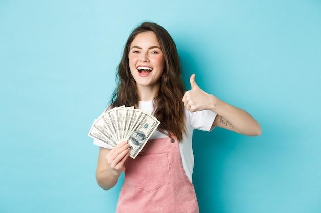 Lächelnde glückliche frau, die geld, dollarnoten hält und den daumen nach oben zeigt, einen schnellen barkredit empfiehlt und zufrieden aussieht, auf blauem hintergrund stehend