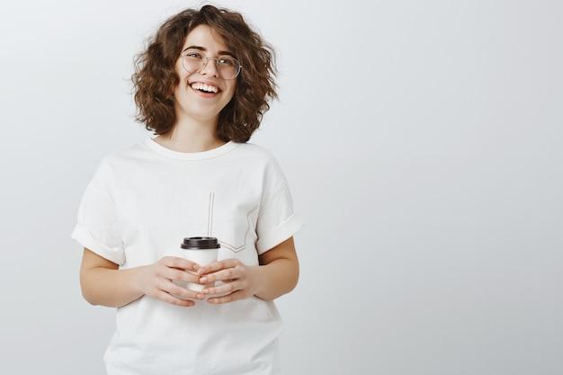 Lächelnde glückliche frau, die kaffee trinkt und über graue wand lacht