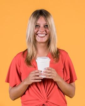 Lächelnde glückliche frau, die wegwerfkaffeetasse hält