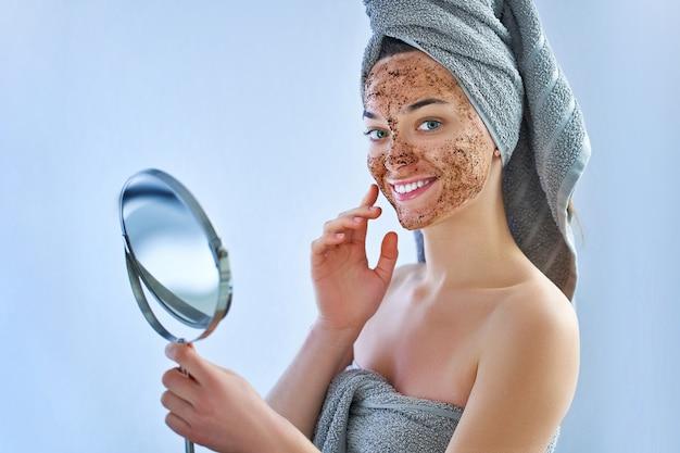 Lächelnde glückliche frau im badetuch mit natürlicher reinigungsgesichtskaffee-peelingmaske nach dusche
