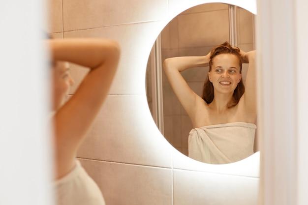 Lächelnde glückliche frau mit perfekter haut, die mit erhobenen armen vor dem spiegel im badezimmer steht, morgenroutine, attraktives weibliches eingewickeltes weißes handtuch.