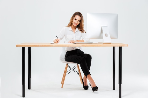 Lächelnde glückliche geschäftsfrau, die dokumente unterschreibt, während sie am schreibtisch sitzt