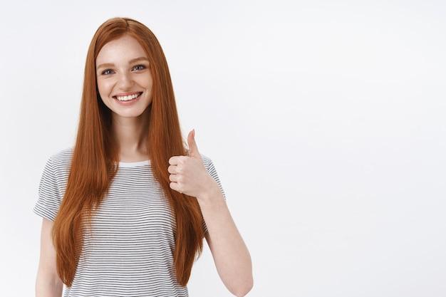 Lächelnde glückliche ingwer-studentin zeigt daumen hoch lächelnd erfreut, empfehlen stolz gutes produkt, stimmen wie gutes essen zu, genehmigen interessantes konzept, weiße wand