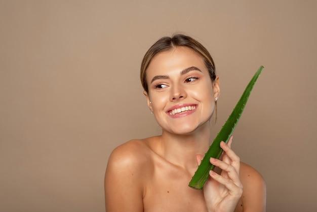 Lächelnde glückliche junge frau, die aloe-blatt in ihren händen auf beigem hintergrund hält. das konzept der hautpflege, die mit naturkosmetik befeuchtet.