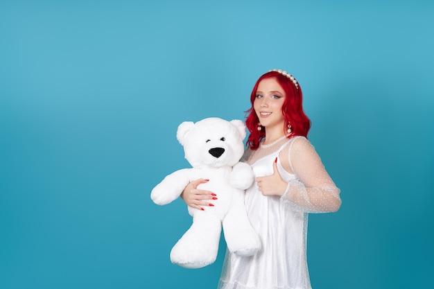 Lächelnde glückliche junge frau im weißen kleid mit den roten haaren hält weißen teddybär und gibt daumen auf