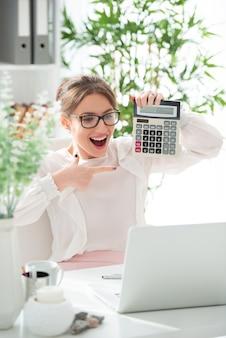 Lächelnde glückliche junge frau in gläsern mit taschenrechner im büro. erfolgreicher ausgleich.