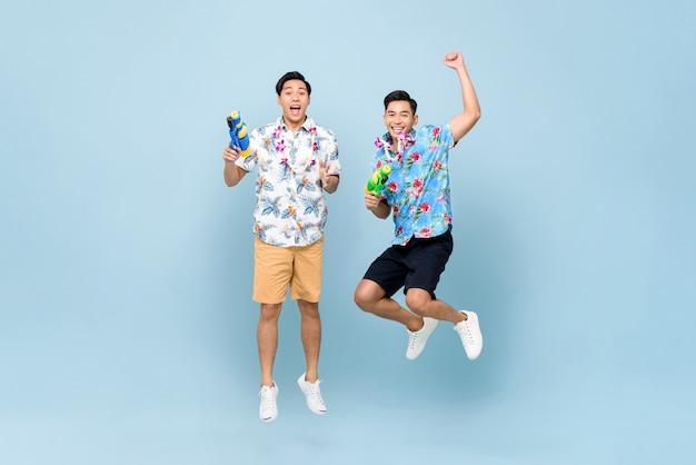 Lächelnde glückliche männliche freunde, die mit wasserpistolen spielen und für das songkran-festival in thailand und in südostasien springen