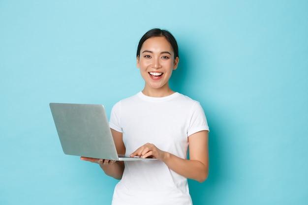 Lächelnde glückliche, schöne asiatische frau, die laptop benutzt, während sie über hellblauer wand steht, fröhliche haltung ausdrückt, am projekt arbeitet oder online einkauft