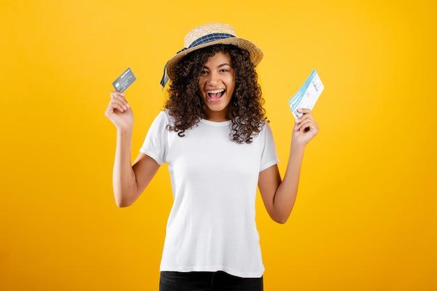 Lächelnde glückliche schwarze frau mit den flugtickets und tragendem hut der kreditkarte lokalisiert über gelb