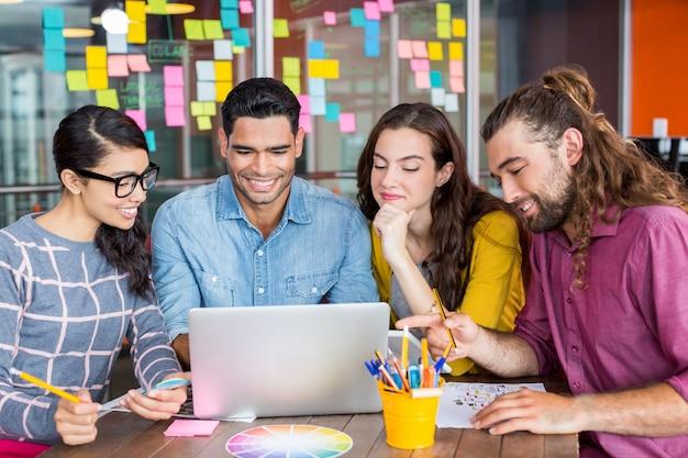 Lächelnde grafikdesigner diskutieren über laptop in besprechung