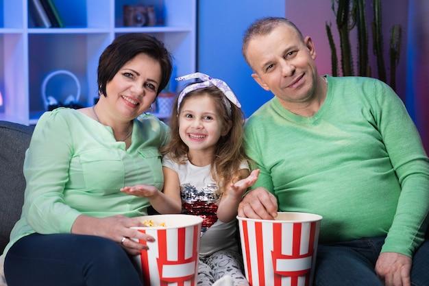 Lächelnde großeltern und enkelin mit enkelin, die zu hause auf dem sofa sitzt. großvater und großmutter mit enkelin sitzen auf sofa zu hause und schauen sich einen film an.