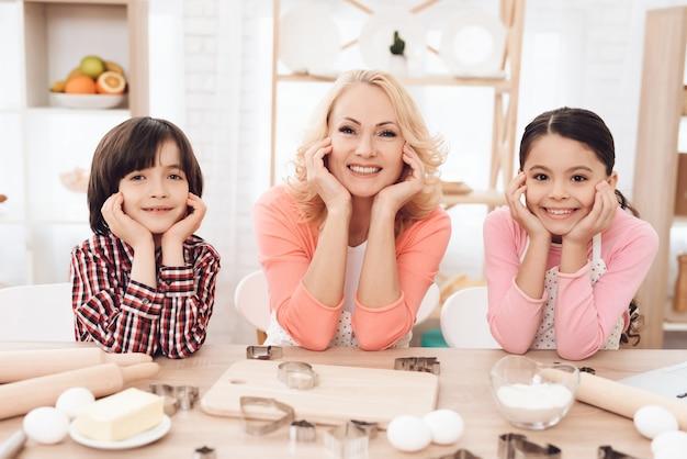 Lächelnde großmutter mit enkelkindern betrachten kamera