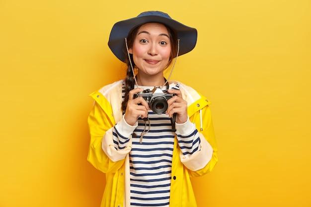 Lächelnde gut aussehende asiatische frau mit langem zopf, trägt hut, gelben regenmantel, hält retro-kamera, macht fotos während ihrer fantastischen reise, isoliert über gelber wand