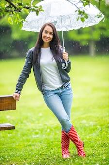 Lächelnde gut aussehende frau lehnt sich an eine parkbank, die unter dem regenschirm geschützt ist.