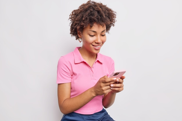 Lächelnde, gut aussehende frau mit lockigem haar verwendet das handy zum senden von textnachrichten und zum scrollen von newsfeeds in einem lässigen rosa t-shirt isoliert über weißer wand