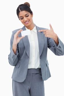 Lächelnde händlerin, die auf leere visitenkarte zeigt