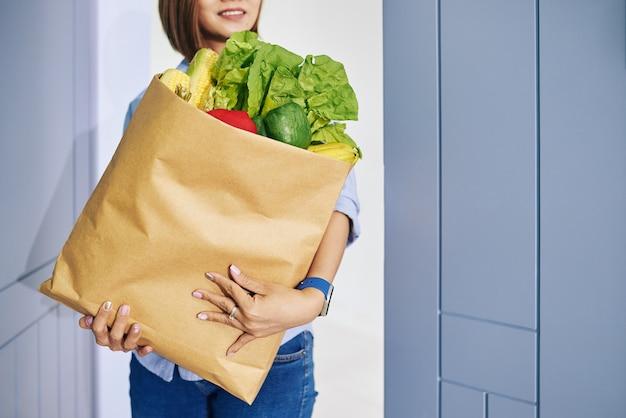 Lächelnde hausfrau bringt großes paket mit frischen lebensmitteln nach hause