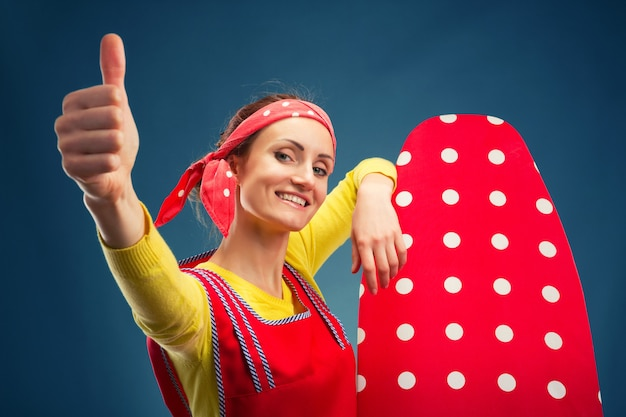Lächelnde hausfrau mit bügelbrett
