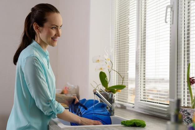 Lächelnde hausfrau wäscht sich in der spülbeckenblauplatte