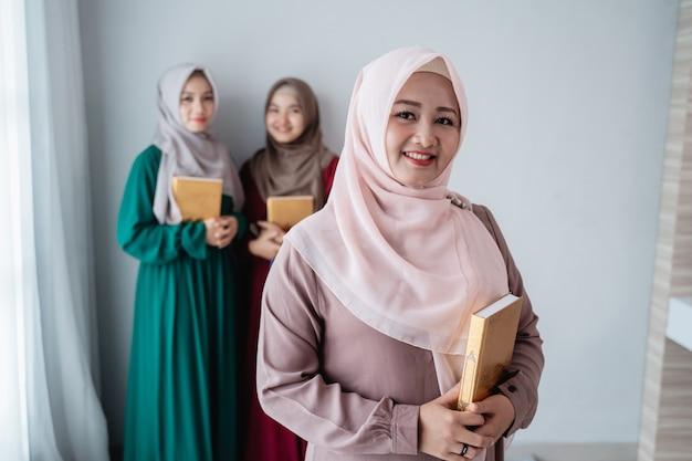 Lächelnde hijab-frauen halten das heilige buch al-quran