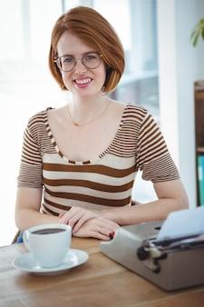 Lächelnde hippie-frau an einem schreibtisch mit kaffee und einer schreibmaschine