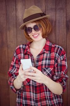 Lächelnde hippie-frau auf ihrem smartphone
