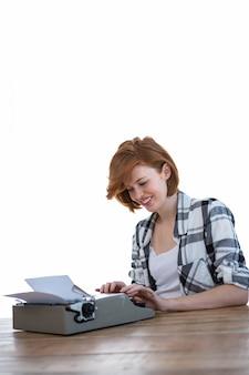 Lächelnde hippie-frau, die an einem schreibtisch, schreibend auf ihrer schreibmaschine sitzt