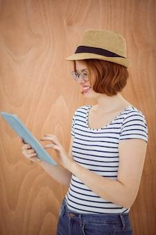 Lächelnde hippie-frau, einen trilby tragend, auf ihrem tablet-computer